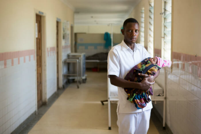 WaterAid wants to bring safe clean water to hospitals, to avoid sepsis in newborns. Daniel, pictured here, is a midwife.